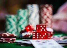 Fichas de casino apiladas y dados en una mesa de casino