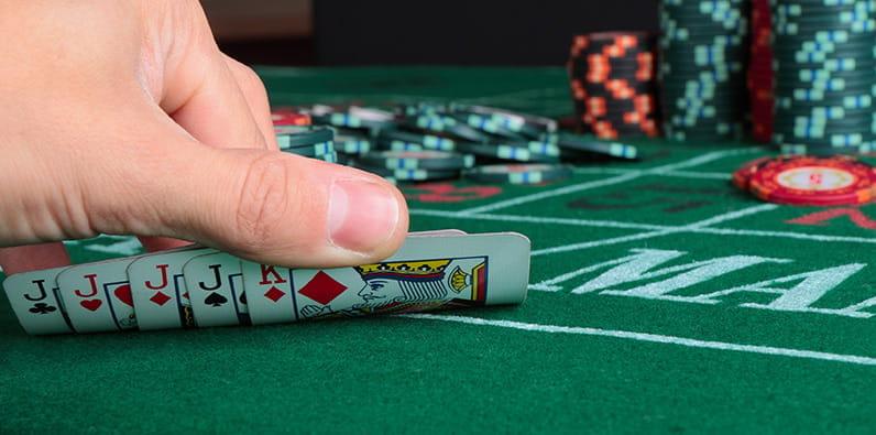 Jugador mostrando sus cartas en una mesa de póker