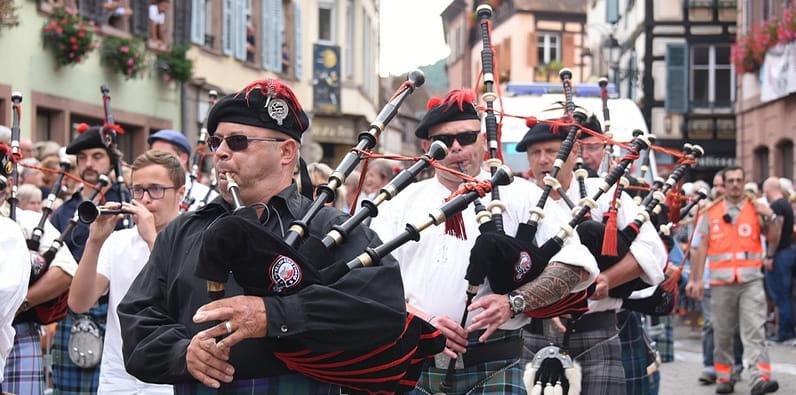 Grupo de hombres en la calle que son vestidos con ropa tradicional escocesa y tocan gaitas