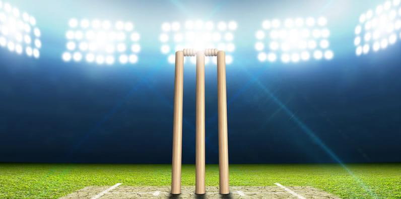 Bola merah, sarung tangan, dan pemukul kriket di halaman stadion