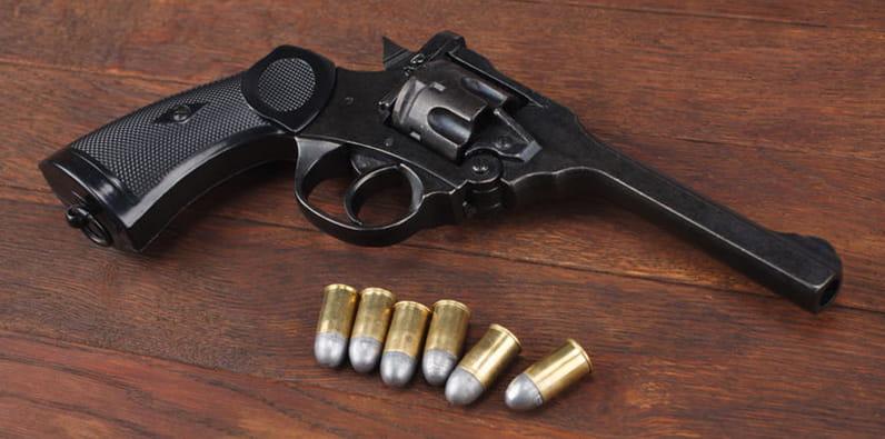 Sebuah revolver dan enam peluru di atas meja